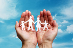 Papierkettenfamilie geschützt in schalenförmigen Händen Stockbilder
