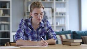 Papierkowa robota, młodej kobiety Writing podczas gdy Siedzący na biurku zbiory wideo