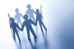 Papierleute, die zusammen Hand in Hand stehen Team, glabal Geschäftsverbindungskonzept Lizenzfreie Stockfotos
