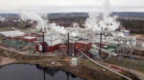 Papiermühle in Borlänge, Schweden mit rauchenden Schloten Schattenbild des kauernden Geschäftsmannes Stockfoto