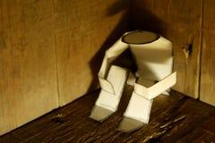 Papiermann in einer dunklen Ecke Stockbild