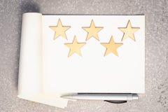 Papiernotizbuch, fünf hölzerne Sterne und Stift stockfotos