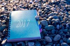 Papiernotizbuch mit dem Text 2017, der auf am Seestrand liegt Lizenzfreie Stockbilder