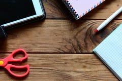 Papiernotizbuch, Tabletten-PC, Stift, Scheren auf einem hölzernen Hintergrund mit leerem Platz für Text Modernes Arbeitsplatzkonz Stockfotos