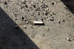 Papierosowy krupon z popiół betonową podłogą papierosowi krupony z popiółu zbliżeniem zdjęcie stock