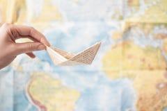 Papierowa łódź robić stary drukowany papier na światowej mapy tle Podróży morza pojęcie Fotografia Stock