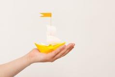Papierowa łódź w ręce na białym tle Zdjęcia Stock