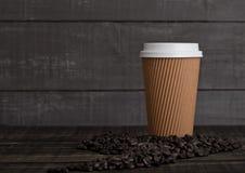 Papierowa filiżanka z cappuccino i kawowymi fasolami zdjęcie royalty free