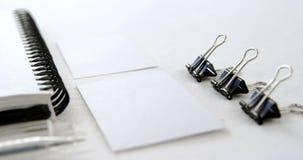 Papierowa klamerka, odwiedza kartę, organizatora i pióra na białym tle 4k, zdjęcie wideo