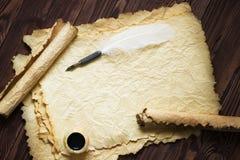 Papierowa ślimacznica z piórkowym piórem i atrament puszkujemy na drewnianym tle Obraz Stock