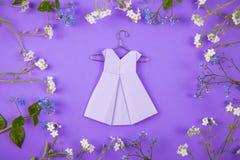 Papierowa origami suknia na wieszaku otaczającym z błękitnym i bielem zaświecającymi Obraz Royalty Free