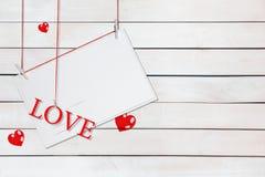 Papierowa pocztówka i słowo miłość wiesza na czerwonych niciach otaczać sercami z kopii przestrzenią na białym drewnianym tle obrazy royalty free