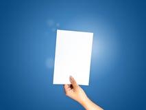 Papierowa ręka trzyma dalej błękitnego gradient Zdjęcia Stock