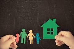 Papierowa rodzina i dom w rękach fotografia stock