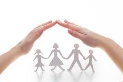 Papierowa rodzina pod rękami w gescie ochrona fotografia stock