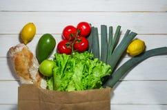 Papierowa torba różny zdrowia jedzenia biały drewniany tło obraz royalty free