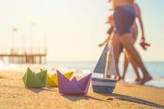 Papierowe łodzie, drewniana łódź i odprowadzeń ludzie przy plażą, fotografia royalty free