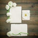 Papierowe karty i koperta z białymi kwiatami na drewnianym tle Mieszkanie nieatutowy, odgórny widok ornamentu geometryczne tła ks Fotografia Stock
