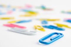 Papierowe klamerki na białym tle - selekcyjna ostrość Fotografia Stock
