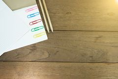 Papierowe klamerki na notatniku z ołówkami na drewnianym stole obrazy royalty free