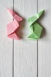 Papierowego origami handmade menchia, zieleni króliki na białym deski stajni drewnie wsiada tło Zdjęcie Stock