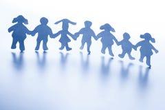 Papierowi dzieci stoi wpólnie ręka w rękę Fotografia Stock