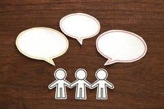 Papierowi ludzie z kolorową pustą dialog mową gulgoczą na brown drewnie czarny komunikacji koncepcji odbiorców telefon Zdjęcia Stock