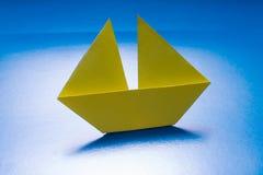 Papierowy Łódkowaty żeglowanie na Błękitnego papieru morzu. Origami statek Zdjęcia Stock
