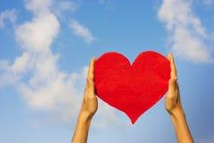 Papierowy czerwony serce w ręce na nieba tle Obraz Stock