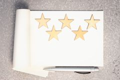 Papierowy notatnik, pięć drewniani gwiazd i pióro, Zdjęcia Stock