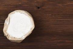 Papierowy pakunek pszeniczna mąka na drewnianym tle Odgórny widok, c zdjęcie stock