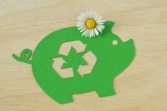 Papierowy zielony prosiątko bank z przetwarzać symbol i stokrotka kwitniemy - pojęcie pieniądze, ekologia i przetwarzać oszc obraz royalty free