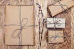 Papierpakete eingewickelt und im Kraftpapier auf einem Holztisch gebunden Abbildung der roten Lilie Beschneidungspfad eingeschlos Stockfotos