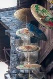 Papierregenschirm, der an einem Haus hängt Stockbilder