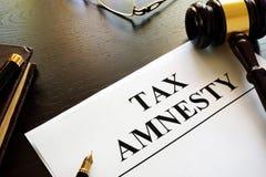 Papiers au sujet d'amnistie d'impôt dans une cour Photos stock