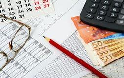 Papiers avec les chiffres, le calendrier, les verres, le crayon rouge, les euros et le Ca image libre de droits