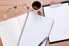 Papiers, bloc-notes et café sur le fond en bois Image libre de droits