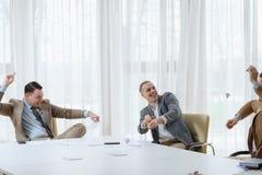 Papiers d'hommes d'affaires rencontrant l'amusement de coupure puéril image libre de droits