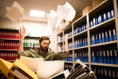 Papiers de lancement irrités d'homme d'affaires dans la chambre de stockage de fichier photos libres de droits