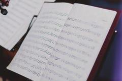Papiers de note sur le support de note de musique Photographie stock libre de droits