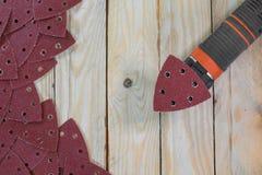 Papiers de sable de triangle sur les conseils en bois avec la ponceuse en bois Images stock