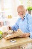 Papiers du relevé d'homme aîné au déjeuner Photos libres de droits