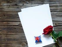 Papiers sur la table avec la rose et le cadeau de rouge Image stock
