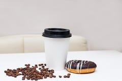 Papierschale mit Kaffee und Donut auf einer weißen Tabelle Stockfotografie