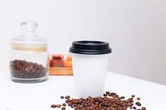 Papierschale mit Kaffee und Kaffeebohnen Stockfoto