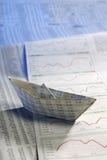 Papierschiff auf Aktienpreisen Lizenzfreies Stockfoto