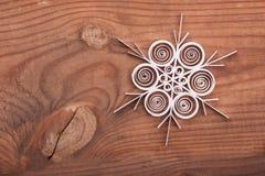 Papierschneeflocke gemacht mit Rüschentechnik auf einer Holzoberfläche Stockfotos