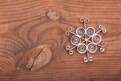 Papierschneeflocke gemacht mit Rüschentechnik auf einer Holzoberfläche Stockbild