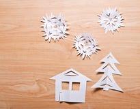 Papierschneeflocken, Haus und Weihnachtsbaum auf hölzernem Stockfotos