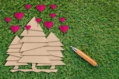 Papierschnitt des Baums und des rosa Herzens auf grünem Gras Stockfotografie